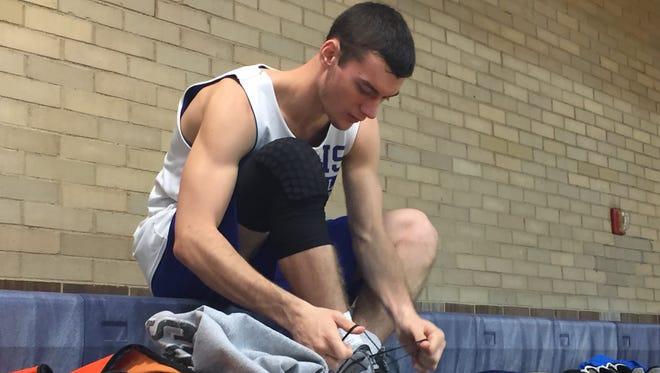 Burris senior Ryan Morey unties his shoes after practice. Burris has early practices, usually starting at 5:45 a.m.