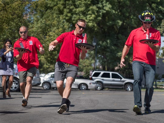Visalia firefighters Will Binder, left, Chris Bailey, and Allen Wilkinson practice Wednesday for the annual Waiters Race on Thursday, August 21, 2017. Firefighters will go up against police officers to benefit charity.