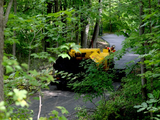 Josh Brooks, right, and Don Castleberry, in gray, both of Superior Asphalt, work on putting down the first layer of asphalt on the walking/running/biking trail around Hawk Island Monday, August 15, 2016 in Lansing. The crews hope to have the 1.5 mile trail complete by Friday. The trial will remain closed as they work on it.