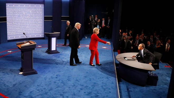Democratic presidential nominee Hillary Clinton, center, and Republican presidential nominee Donald Trump greet moderator Lester Holt after the presidential debate at Hofstra University in Hempstead, N.Y.