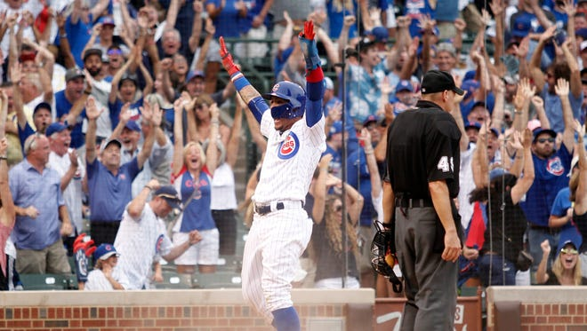 Chicago Cubs second baseman Javier Baez (9) celebrates after scoring the game-winning run off catcher Alex Avila's single in the 10th inning.