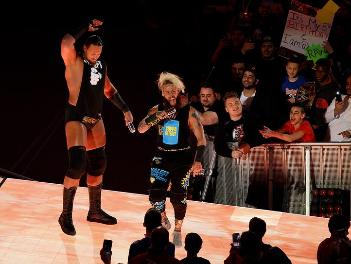 Enzo Amore, right, and Big Cass walk toward the ring