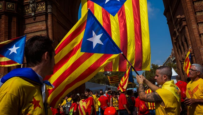 People wave flags that symbolize Catalonia's independence in Barcelona, Spain, on Sept 11, 2014.