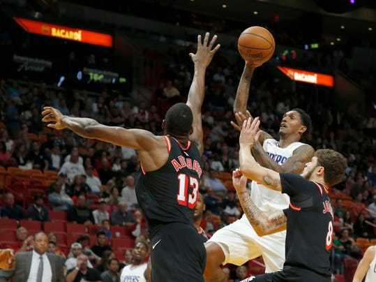 Los Angeles Clippers guard C.J. Williams (9) shoots between Miami Heat defenders Bam Adebayo (13) and Tyler Johnson (8) in the second quarter of an NBA basketball game, Saturday, Dec. 16, 2017, in Miami. (AP Photo/Joe Skipper)