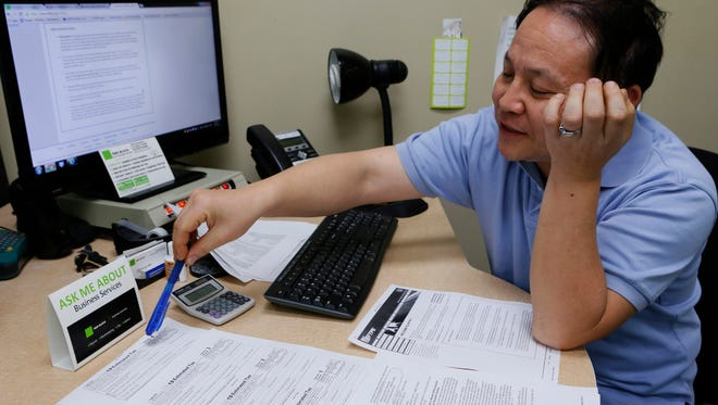 H&R Block public accountant John Lee explains how to file the 2013 1040-ES IRS Estimated Tax forms at his office in the Echo Park district of Los Angeles.