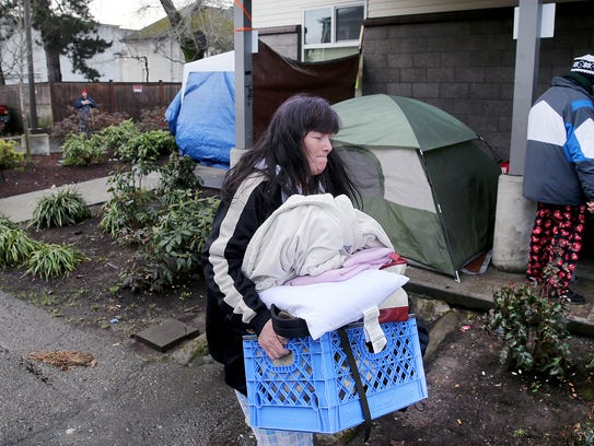 Tami Fields carries her belongings outside the downtown Bremerton Salvation Army, which was closed Wednesday due to an outbreak of bed bugs.