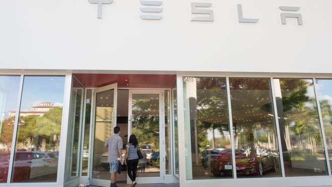 Customers enter the new Tesla store at Waterside Shops in Naples, Fla., on Dec. 20, 2016.