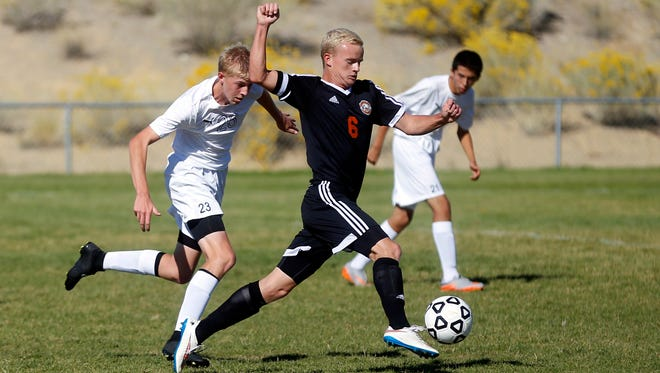 Aztec's Riley Barber is chased by Piedra Vista's Richard Cross during a match on Saturday at the Piedra Vista High School soccer fields in Farmington.