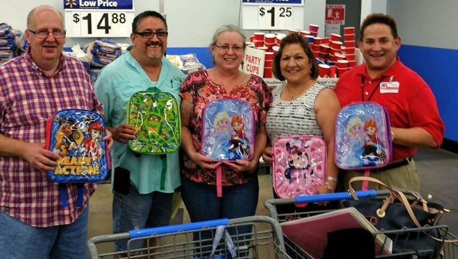 Board members of The Loving Spoonful, a local nonprofit, sponsored a school clothes and supplies shopping expedition for 82 children that are infected or affected by HIV/AIDS. Board members include Raymond Pokorny (from left), Jerry Ysaguirre, board President Darlene Lee-Omana, and Minnie Perez and Alfred Blancas, volunteers from the Coastal Bend Wellness Center.