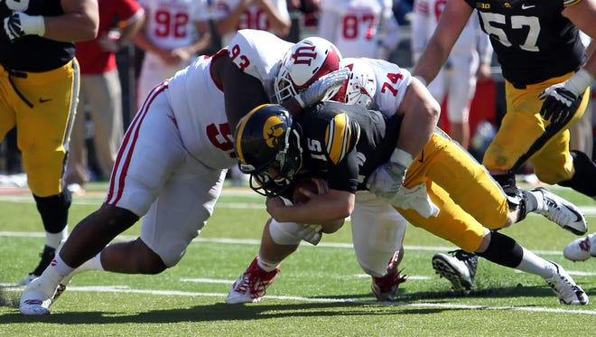 Iowa QB Jake Rudock (15) is tackled for a loss by Hoosiers defensive tackle Ralph Green III (93) and defensive tackle Nate Hoff (74).