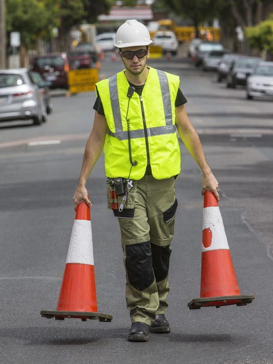 Traffic controller holding witch's hats in both hands