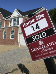 A sold sign stands in front of a home under construction