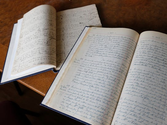 Log books from the mid-1800s of baptisms and deaths