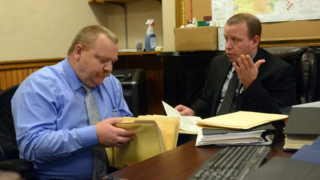 Fairfield County Sheriff's Office Detectives Andy Robberts, left, and Jason Meadows look over case files for the department's two cold homicide cases — those of John Landis and Randy Winegardner.