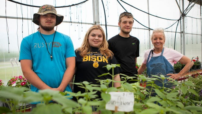 From left to right, Buffalo Gap students Arion Nycum, Megan Horn and Chip Dovel stand with the school's agriculture teacher, Debbie Strole, in the greenhouse during their spring plant sale on Friday, May 15, 2015. The three students in the class put in over 200 hours of combined time growing hundreds of flowers, vegetables and herbs to fill the greenhouse for the sale.