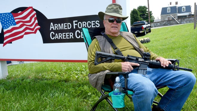 "Dave Beisner sits with a short barrel rifle in his lap as he keeps watch outside the Armed Forces Career Center on Richmond Road, a task he volunteered to do as a private citizen, in Staunton on Thursday, July 23, 2015. What we're doing here is providing protection for the recruiting officer until something more substantial is provided by either the Federal government or the state,"" said Beisner. ""This is in the wake of Chattanooga, Tennessee, and other things.""  He states he served seven years in the Army and 20 years with the FBI."