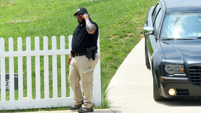 A member of a security detail maintains watch outside a residence on South Windsong Court in Fishersville on Monday, June 27, 2016.