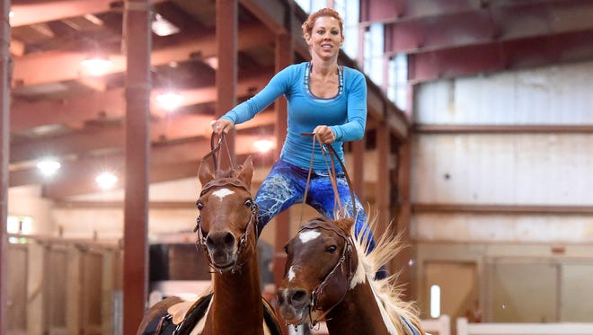 Fairland Ferguson demonstrates her skill at Roman riding, riding two horses at one time around the show ring. She she holds onto the reigns and stands on the backs of her horses, Hondo and Little Joe, at Virginia Horse Center in Lexington on Friday, Oct. 7, 2016.