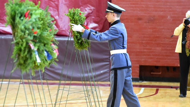 A cadet places one of several wreaths honoring veterans during the Wreaths Across America ceremony held at Fishburne Military School on Tuesday, Dec. 13, 2016.