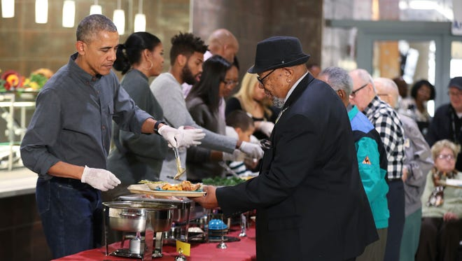 President Barack Obama, left, with first lady Michelle Obama and some relatives serve Thanksgiving meals to residents of the Armed Forces Retirement Home in Washington, Wednesday, Nov. 23, 2016.