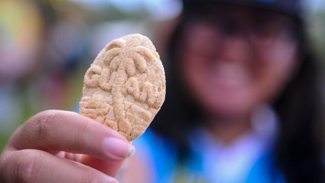 Jaden Belga display a Chamorro rosquete cookie in the shape of the Guam seal as she and her mother visits the 28th Annual Guam Micronesia Island Fair at the Gov. Joseph Flores Memorial Park in Tumon on June 12.
