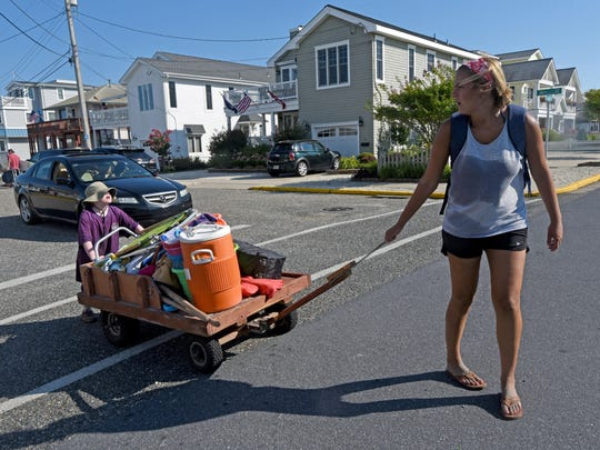 At the end of an afternoon at the beach in Avalon, Diller camper Andy Fass, 8, of Hamilton, helps counselor Jill Forst get the wagon of shore supplies back to the house two blocks faway.
