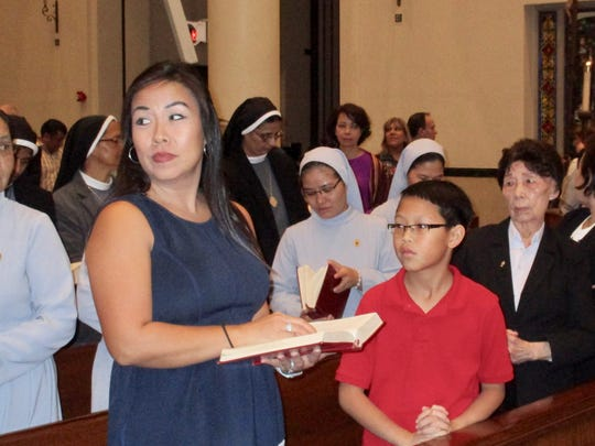 The Rev. Hanh Van Pham's sister Rose Pham Tran (from left), nephew Jadon Tran and mother Huong Pham attend a Mass of thanksgiving celebrating the 25th anniversary of his ordination to the priesthood Friday, Jan. 20, 2017, at the Corpus Christi Cathedral.