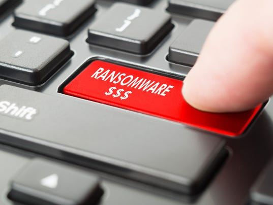 Ransomware written on keyboard button with finger pressing on it