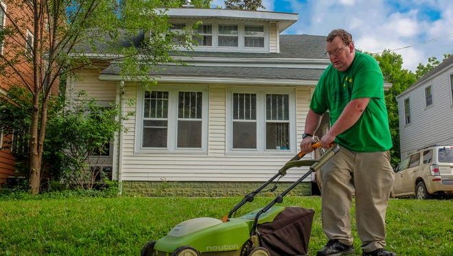 Matt Arends mows the lawn at the house where he rents a room near Sparrow Hospital Wednesday, July 19, 2017.