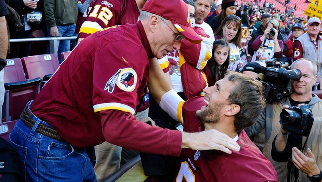 Washington Redskins quarterback Kirk Cousins (8) celebrates with his father Don Cousins (L) after defeating the New Orleans Saints 47-14 at FedEx Field.