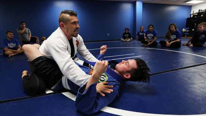Ida Baker teacher Josh Franzke demonstrates an exercise during his self defense class Tuesday afternoon. Franzke started a self defense program for its students. The program is in its third year and provides a cross section of training for students including wrestling and jiujitsu among others.