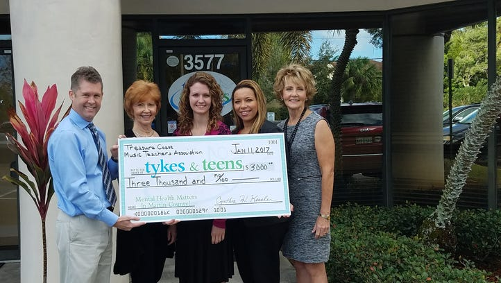 A $3,000 donation is presented to Tykes & Teens by