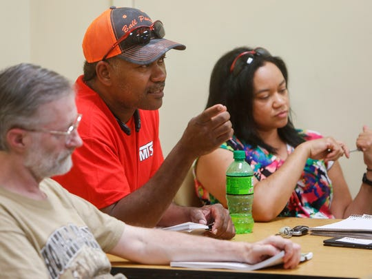 Jim Ball, center, of Moore's Trash Services, asks a