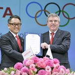 International Olympic Committee President Thomas Bach, right, and Toyota President Akio Toyoda hold their agreement document to become part of the IOC's top sponsorship program in Tokyo