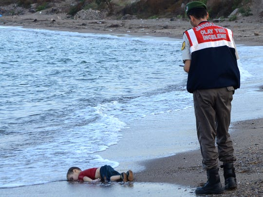 A Turkish police officer stands next to the body of 3-year-old Syrian boy who drowned in the Mediterranean Sea in 2015 after a boat carrying refugees sank.