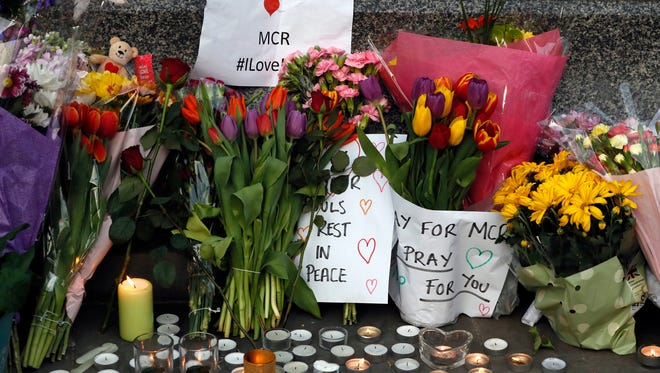 People lay flowers after a vigil in Albert Square, Manchester, England.
