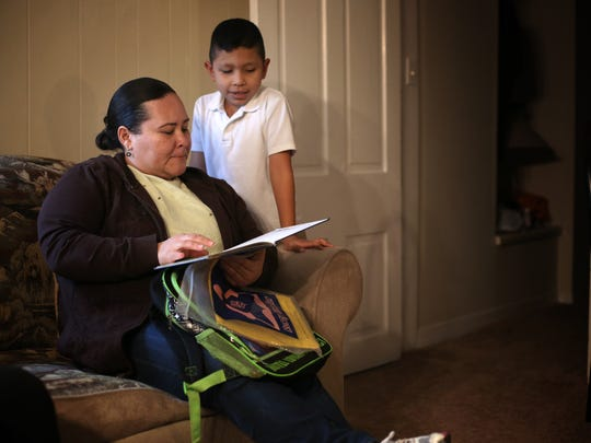 Miriam Zelaya, looks over school work with her son, Fernando Sierra, 7, in their Carthage apartment on January 25. Zelaya is from Tegucigalpa, Honduras, where she owned and operated a small men's clothing store. She received call from a man with Mara 18 gang in May 2014, telling her she needed to pay about $75 weekly for rent on her store. She refused and went into hiding with her son. She lived safely inside her best friend's home for about a year, until the gang found her on July 12, 2015. She crossed the border illegally at Matamoros, Mexico. Zelaya and her son were detained and registered and currently seeking asylum in fear for their lives if they were to return to Honduras.
