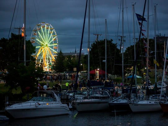 A ferris wheel is seen beyond masts during Boat Night