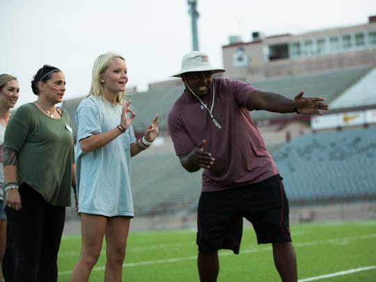 New Mexico State graduate assistant coach Kai Brown, right, instructs Erica Martin on how to perform a tackle during the Aggies Women's Clinic at Aggie Memorial Stadium.