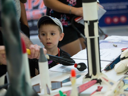 Tucker Simpson, 4, looks on as Scott Runyen, with the Fellowship of Las Cruces Area Rocketry Enthusiasts or FLARE, talks to him about how model rockets operate during the NASA Downlink program's Science of Space Fair outside of the City Councuk Chambers at Las Cruces City Hall, Tuesday  July 31, 2018.