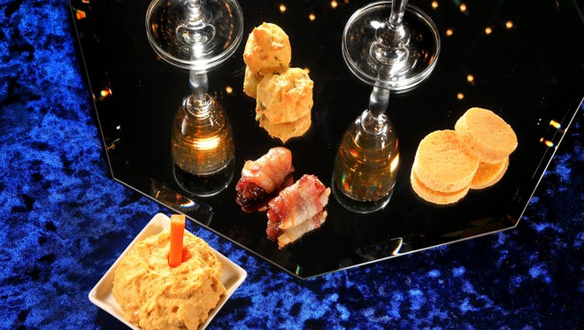 Clockwise from left, Hors d'oeuvres that can be a slam dunk for New Year's Eve parties can include classic Hummus, Bacon-Wrapped Dates with Parmesan, Herbed Gougeres, and 1770 Cheese Biscuits. (Christian Gooden/St. Louis Post-Dispatch/TNS)