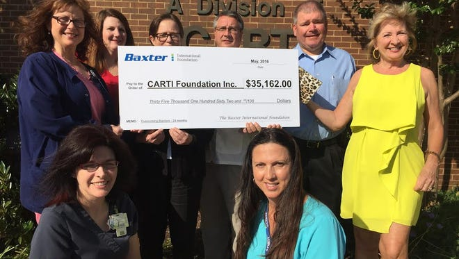 CARTI in Mountain Home receives a $35,162 check from the Baxter International Foundation Tuesday. The money will assist low-income patients with housing and lodging.