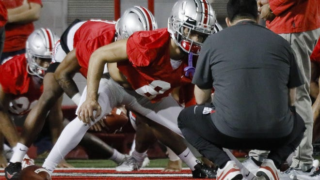 Ohio State Buckeyes wide receiver Chris Olave (2) chats with head coach Ryan Day, right, as he stretches at the start of the first day of spring football practice on Monday, March 2, 2020 at the Woody Hayes Athletic Center in Columbus, Ohio.