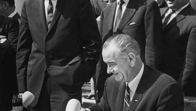 President Lyndon Johnson signs the War on Poverty bill on Aug. 20, 1964, eight months after launching it in his State of the Union.