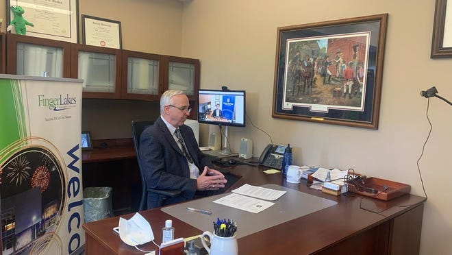 President Robert Nye signs the transfer agreement from his office at the Finger Lakes Community College main campus.