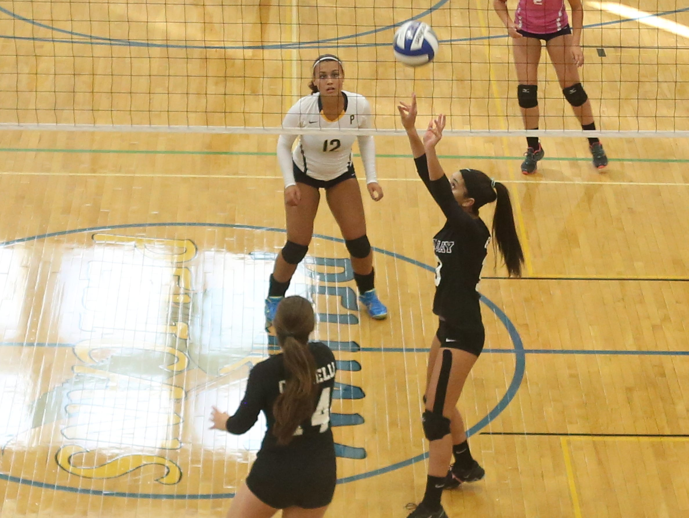 John Jay's Katie Mines sets up a shot for Rachel Cifarelli during a varsity volleyball match against Pelham at Pelham High School Sept. 3, 2015.