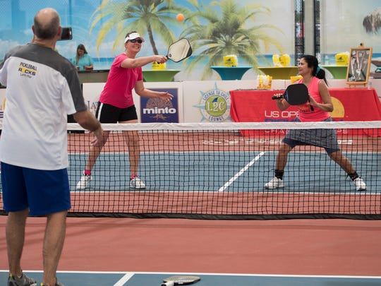 Amateur pickleball players Leslie Najjar, center, and Lily Hencken, right, pose for a photograph by Leslie's husband Mike Najjar, left, on the Zing Zing Championship Court after media day at the US Open Pickleball Championship at East Naples Community Park April 21, 2017. The group is from Saintt Louis.