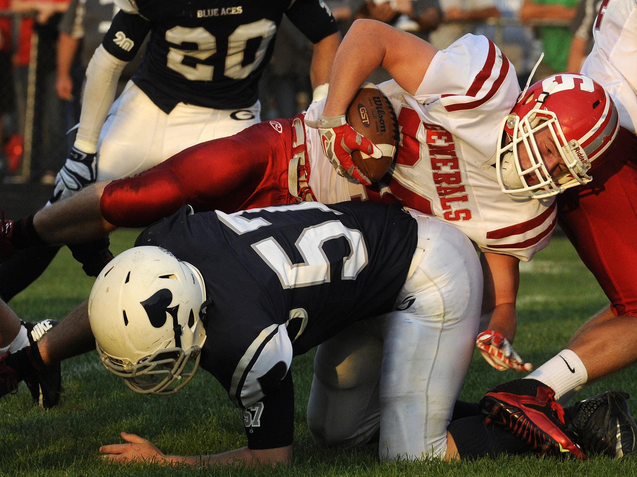 Granville's Mathieu Holt (57) and Andrew Bubnar (20) team up to take down a Sheridan ball carrier during the Blue Aces' season-opening win.