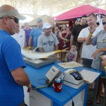 Weigh master Mark Wright, left, certifies a jack crevalle as a crowd gathers at the 2014 Mississippi Deep Sea Fishing Rodeo.