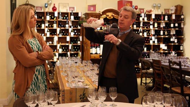 Food writer Megan McCaffrey looks on as lohud wine expert, Thierry Pradines of Best Wine Purveyors in Pleasantville, prepares for an exclusive tasting event at his shop, Feb. 11, 2016.